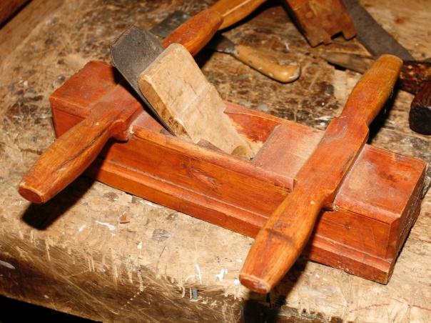 """Skottokse i samlinga på Dølmotunet i Tolga. Høvelen er stempla med bokstavane EI, truleg er det bokstavane til snikkaren som har laga og brukt høvelen. Skottoksen er kring 12 """" lang og kan høvle litt i overkant av 2"""" bredde. Høvelen har meiane laga av same stykke som høvelstokken. Foto: Roald Renmælmo"""