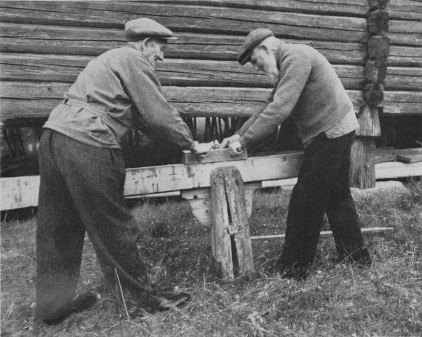 """Når det skulle bygges hus, måtte det bl. a. skaffes grulvplanker. De ble høvlet hjemme på gården , og kantene skulle høvles slik at de kunne felles sammen. Under arbeidet ble bordene festet i en såkalt skottbenk, slik som bildet viser. Det er tatt på Hadelandsmuseet. Foto og billedtekst: Frå boka """" Vår gamle bondekultur"""", Visted og Stigum, 951"""