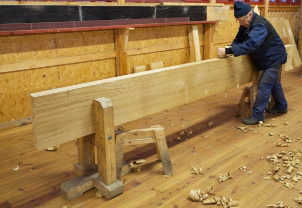 "Tomas Karlsson høvlar kant på benkeplate til høvelbenk. Emnet er 3,8 meter langt, 15"" bredt og 3 1/2"" tjukt. For å få emnet fast på kant spente vi det opp i to lause bukkar til ein skottbenk. Foto: Roald Renmælmo"