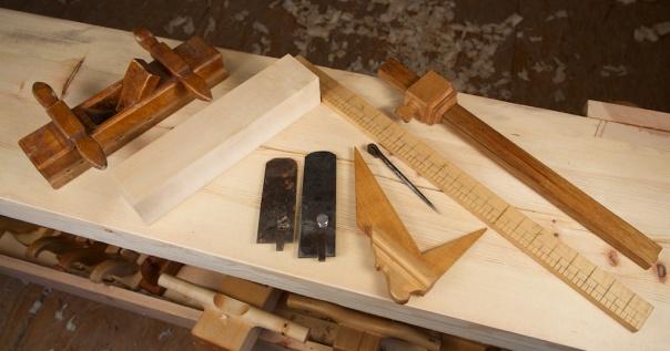 Til venstre er nothøvelen frå kista til Høs-Knut. Midt på biletet er høvelståla, til venstre det gamle og til høgre ein nysmidd kopi. Emnet ved sida av høvelen er til den nye høvelen som er under produksjon. Foto: Roald Renmælmo