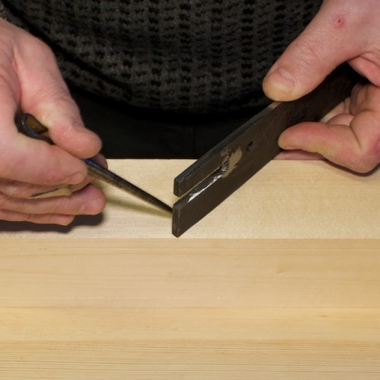 Her legg eg høvelstålet mot streken for senga og merkar av tjukna på stålet. Foto: Roald Renmælmo