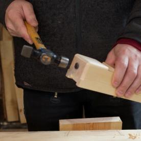 Eg slår inn slagknappen med hammar. Fordelen med ein slagknapp av jarn er at det er lettare å justere høveltanna med ein liten hammar og ein sparar slitasje på høvelstokken. Foto: Roald Renmælmo
