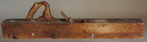 """Langhøvel med lengd på 26 ½ norsk tomme. Tanna er 2 ¼"""" brei av merket Ward & Paine, truleg etter 1840. Handtaket er stilt litt mot høgre side av høvelstokken slik som er vanleg på eldre høvlar. Høvelen har ikkje klaff på tanna. Høvelstokken er kring 3 ⅛"""" høg og laga av bjørk. Slitasjen etter hendene viser tydeleg at brunfargen er slitt bort. Høvelen er merka med bokstavane PP.N. Senga til høvelstålet ligg på ca 47 grader. Foto: Roald Remælmo"""