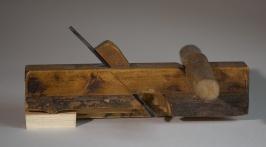 """Nothøvel med tverrhandtak påspikra framme. Høvelen er 10 ¼"""" lang og av bjørk. Senga til stålet ligg på ca 47 grader. Høvelen har ikkje merking. på stål eller høvelstokk. Foto: Roald Renmælmo"""