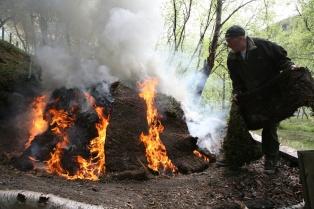 Sverre legger torv på sida av dei stadene som har tatt skikkeleg fyr. Han følger med at det begynnner å brenne under torvene. Foto: Roald Renmælmo