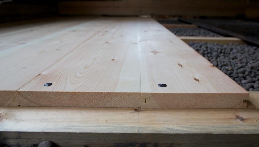 """Nylagte golvbord lagt på tilfararar. I mitt hus har eg ei betongplate som golva kviler på. Oppå denne er det lagt tilfarara av 3"""" x 4"""" som golvborda vert spikra i. Midt på der flakskøyten blir ligg det ein 3"""" x 6"""" på flasken for å ha meir å spikre i. TIlfararane er høvla rette oppå og lagt på klossar som fordeler trykket på betongplata. Mellom tilfararane er det lagt lecakuler som isolasjon mellom betongplata og golvborda. Dette er ei moderne løysing men golvlegginga ser ut til å fungere på same måten som med golvåsar med sand som isolasjon. Det ville vore den eldre tradisjonelle løysinga i mitt område. På biletet ser vi endeveden på borda der flakskøyten kjem. Borda er spikra med smidd spikar. Foto: Roald Renmælmo"""