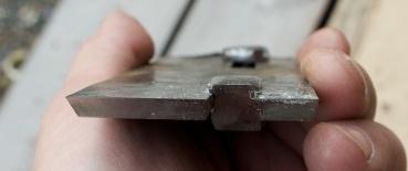 Fjørhøvelstålet sett framafrå. Det er fila ut eit spor i sida på den smale tanna i midten slik at ho passar inn i spalta i det store stålet. Det sikrar at ståla vert stabile under høvling. Så fremt stålet er tilpassa godt i stokken og kilen er god så blir det nok lite vibrasjon i høvlinga. Foto: Roald Renmælmo