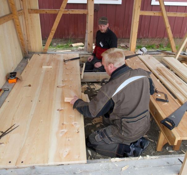 Eit hus som tidlegare var bygd på kurs var objektet som vi skulle panele og spikre golv i. Her held to av deltakarane på og spikrar golvborda som er høvla på kurset. Foto: Roald Renmælmo