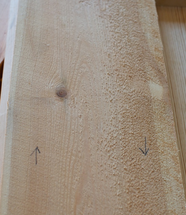 Bord som er saga av tømmer som er vindt, altså høgrevridd, vil få motved på høgre side og medved på venstre side. Her er det markert med piler med blyant. Når eg høvlar slike bord ser eg med eint gong på strukturen i overflata på bordet at veden går mot den retninga eg høvlar. Biletet er tatt med baklys frå vindauget og då vert det skygge av  fibrane som står opp i høgre side av bordet. Venstre side ser glattare ut. Foto: Roald Renmælmo