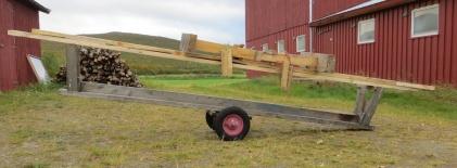 Tømmertralla Arne brukar til å flytte stokkar er ypperleg for å transportere skottbenken og langbenken. Då har han eit mobilt golvbordhøvleri. Foto: Arne Graven