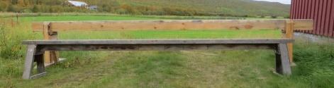 På garden i Sirma kom Arne over denne langbenken som er enkelt laga men ser ut til å fungere veldig bra. I standen for å stivast av med sargar på sidene eller ved å ha ein tjukk planke i setet så har ein lagt ein smalare planke på høgkant under setet. Slik kan ein byggje ein smekrare benk. Benken er 56 cm høg og 3,64 cm lang. Foto: Arne Graven