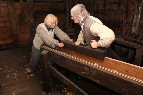 """""""statister"""" høvler kanten på et bord i snekkerutstillingen i """"Den gamle by"""" i Århus."""