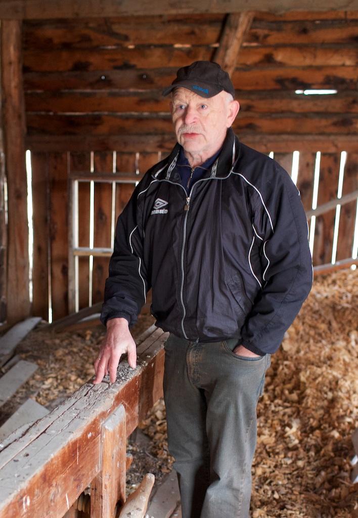 Peder Evjen ved sida av skottbenken og med høvelspona frå sist benken var i bruk. Foto: Roald Renmælmo
