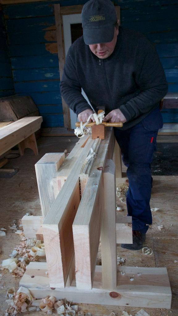 Høvling av golvbord med fjørhøvel på skottbenk. Av Konrad Stenvold har eg lært korleis ploghøvlane fungerer saman med skottbenken. Det er likevel mange sider av arbeidet med skottbenken som eg veit lite om. Då kan eg bruke andre kjelder til å supplere kunnskapen. Foto: Roald Renmælmo
