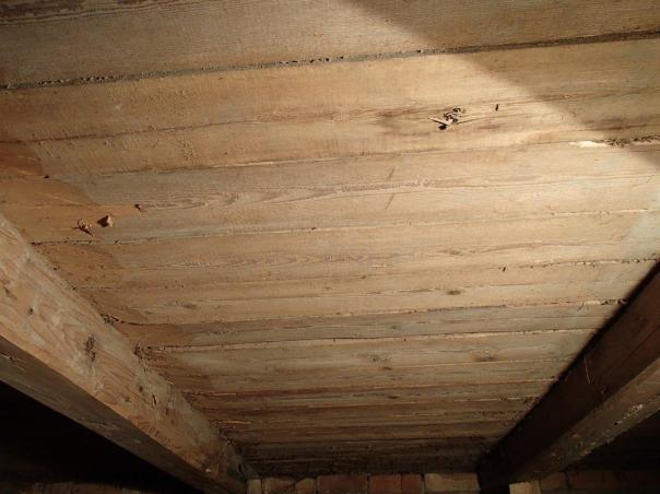 Undersida av golvet med laus fjør. Spora tyder på at det er saga på ei oppgangssag/rammesag. Borda er lagt med marg opp og er hogd til på tjukna for å ligge på åsane. Foto: Magnus Wammen