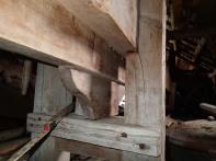 Bildet viser opplegget for bevegelig langplanke; en tilhogd kloss som er spikret. Til høyre fast langplanke hvilende halvt innpå stolpe. Foto: Ivar Jørstad