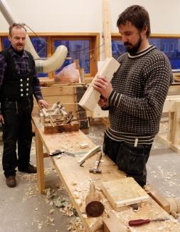 Einar siktar etter sålen på høvelen som han held på å lage. Jon Dahlmo står ved sidan av sine nye golvplogar. Foto: Roald Renmælmo