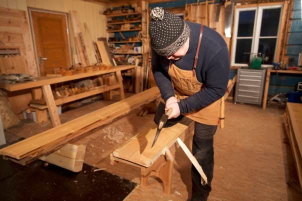 """Kanting av golvbord, eller som Olav Furuset skriv, """"telje tå det grøvste med øks"""". Her er bordet snorslått med sotsnor for å få nokolunde rett kant. Foto: Roald Renmælmo"""